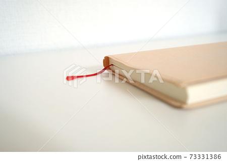 책상에 놓여있는 문고본 사이즈의 심플한 노트북과 붉은 책갈피 73331386