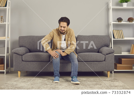 Young man sitting on couch at home and touching his hurt knee with grimace of pain 73332874