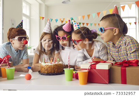 Group of children all together blowing candles on birthday cake at fun party at home 73332957