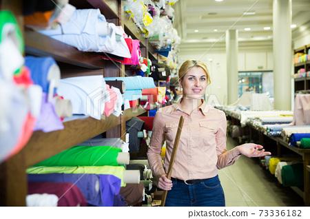 Salesgirl working in fabric store 73336182