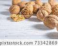 Walnuts kernels on white wooden desk, stock photo 73342869