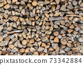 Background of dry chopped firewood logs in a pile 73342884