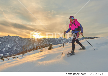Sporty girl with snowshoes in sunset landscape 73345746