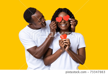 Loving black guy covering his girlfriend eyes with valentine cards 73347863