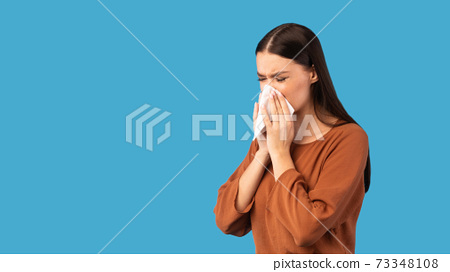 Sick Woman Blowing Runny Nose In Paper Tissue, Blue Background 73348108