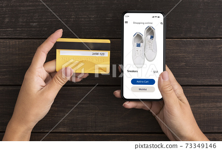 Woman using phone with online clothes store, holding credit card 73349146