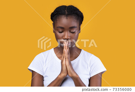 Peaceful African Lady Praying Standing With Eyes Closed In Studio 73356080