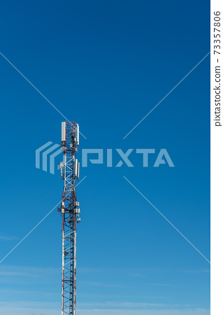Cell phone cell tower for network coverage in front of blue sky 73357806