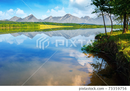 composite landscape of mountain lake in summer. beautiful nature scenery on a sunny morning. sky and ridge reflecting in the calm water surface. trees on the shore 73359756
