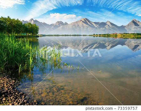 composite landscape of mountain lake in summer. beautiful nature scenery on a sunny morning. sky and ridge reflecting in the calm water surface. trees on the shore 73359757