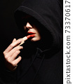 young woman in hood, painting her lips with red lipstick 73370617