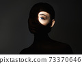 young woman with shadow on the face 73370646