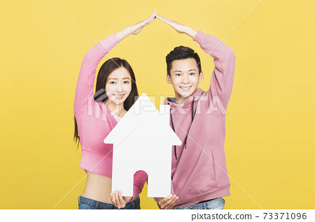 happy young couple holding a small house the in their hands. family and house concept 73371096