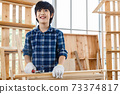 Portrait of happy Asian boy standing in carpentry workshop and holding hammer at home. 73374817