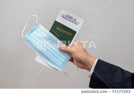 電暈診斷證書,護照和商人的手拿著口罩 73375003