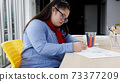 Asian girl with Down's syndrome drawing picture in art class. Concept disabled kid learning. 73377209