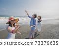 擺在海灘的三青年人 73379635