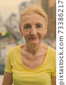Beautiful senior woman with blond hair against view of the city 73386217