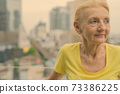 Beautiful senior woman with blond hair against view of the city 73386225