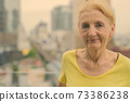 Beautiful senior woman with blond hair against view of the city 73386238