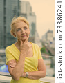 Beautiful senior woman with blond hair against view of the city 73386241