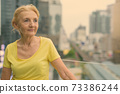 Beautiful senior woman with blond hair against view of the city 73386244