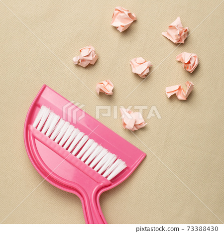 Crumpled paper balls and pink broom on beige fabric background. flat lay, top view, copy space 73388430