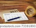 放在木紋桌上的日曆,時間表和時鐘 73391893