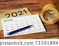 放在木紋桌上的日曆,時間表和時鐘 73391894