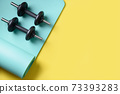 Sport black dumbbells on turquoise yoga mat on yellow. Copy space. View from above. 73393283