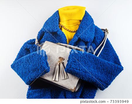Yellow turtle neck with gray handbag, blue coat 73393949