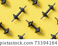 Set of black dumbbells on yellow background. Top view, copy space. 73394164