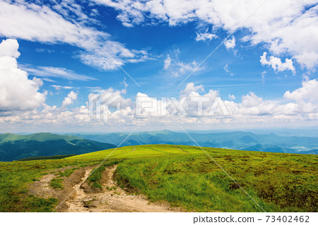 path through green grassy mountain meadow. beautiful summer landscape. fine weather with fluffy clouds on the blue sky 73402462