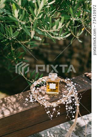 A bottle of perfume and gold wedding rings of the bride and groom on a wooden handrail in a wreath under a tree branch. 73410972