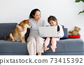 Asian mother and daughter sitting on sofa with their Shiba Inu and using laptop computer together. 73415392