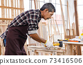 Asian senior man using wallet in woodwork at carpentry workshop. Concept senior people doing hobby after retirement. 73416506