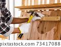 Carpenter use hammer on timber in carpentry workshop. 73417088