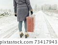 Woman with vintage suitcase in winter 73417943