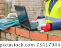 Woman civil engineer holding cup of coffee and using laptop at outdoor 73417944