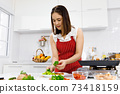 Asian woman chef in red apron putting parsley on steak in kitchen. Concept woman preparing meal at home. 73418159