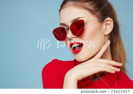 Lovely woman in dark glasses bright makeup red lips glamor blue background 73425457