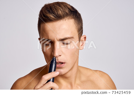 Guy with a trimmer in hand removing hair from the nose naked shoulders emotions light background 73425459