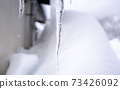 Icicles under the eaves, dripping water. 73426092