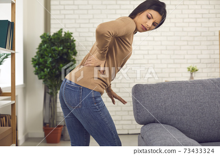 Young woman stands up from sofa and feels sudden intense pain in her lower back 73433324