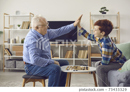 Happy grandfather and grandson high-fiving each other after playing checkers at home 73433329