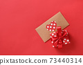 Valentine's day greeting card with gift and love letter on red. Top view. 73440314