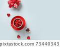 Valentine's day greeting card with red heart sweets, gift and cup on blue. 73440343