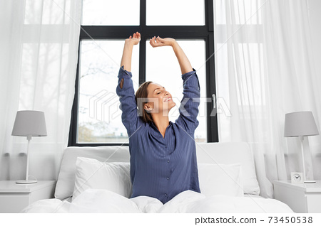 happy woman stretching in bed at home 73450538