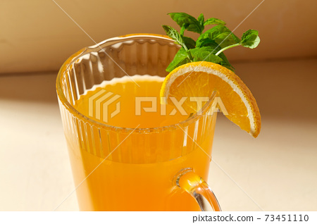 close up of jug with orange juice and peppermint 73451110