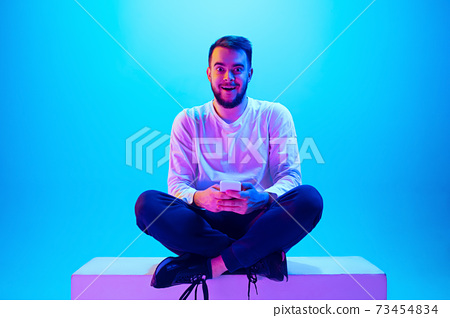 Caucasian man's portrait isolated on blue studio background in neon light. Concept of human emotions, facial expression, sales, ad. 73454834
